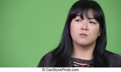 Beautiful overweight Asian woman smiling and thinking -...