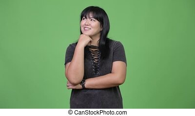 Beautiful overweight Asian woman smiling while thinking -...