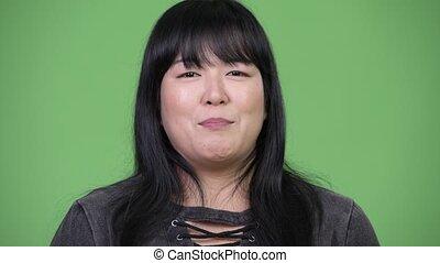 Beautiful overweight Asian woman talking to camera - Studio...