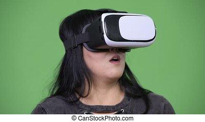 Beautiful overweight Asian woman using virtual reality headset