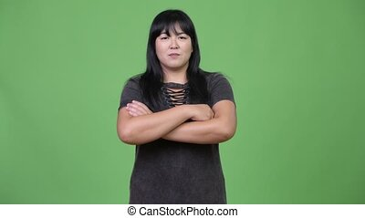 Beautiful overweight Asian woman with arms crossed - Studio...