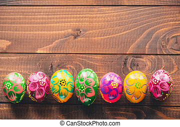 Beautiful painted colorful Easter eggs on old brown wooden background