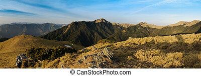Beautiful panorama mountain landscape with golden grassland.
