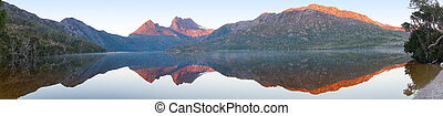 Beautiful panorama of mountain range reflected in lake on sunrise