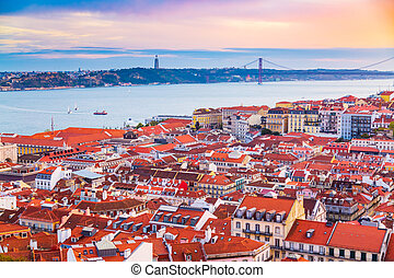 Beautiful panorama of old town Baixa district and Tagus River in Lisbon city during sunset, seen from Sao Jorge Castle hill, Portugal