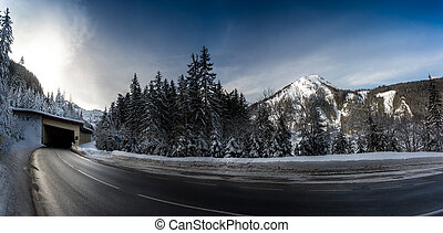 panoramic shot of highway in snowy mountains with long turn