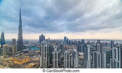 Beautiful panoramic skyline of Dubai timelapse, United Arab Emirates. View of world famous skyscrapers. Aerial top view from tower rooftop. Beautiful cloudy sky. Colourful travel and business background.