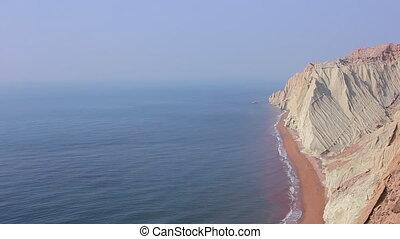 Beautiful panoramic view of the Persian Gulf with colored desert rocky mountains. Hormuz island. Iran