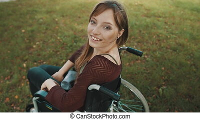 Beautiful paralyzed caucasian woman looking over the shoulder in the park. High quality 4k footage