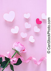 Beautiful pastel pink rose with ribbon and handmade hearts on pastel pink background, top view