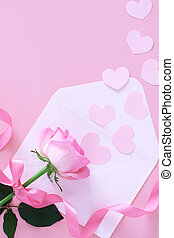 Beautiful pastel pink rose with ribbon ,envelope with small hearts on pastel pink background, top view
