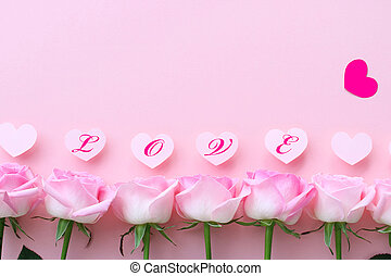 Beautiful pastel pink roses with heart on pastel pink background, top view, space for text