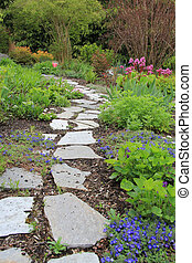 Beautiful paved stone walkway in a spring garden.