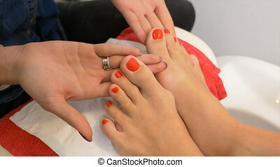Beautiful pedicure with red nail polish presented for evaluation at nail art technician course