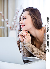 Beautiful pensive young woman using laptop on bed and dreaming
