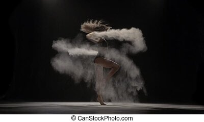 Beautiful performer throwing dust particles in air. Slow motion