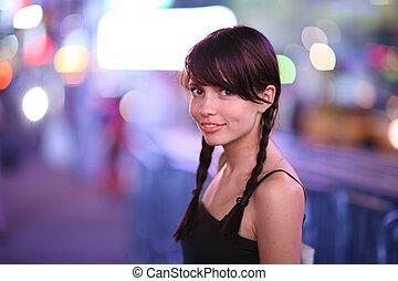 Portrait of beautiful petite woman in night city. Shallow DOF.