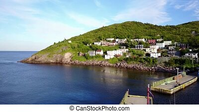 Beautiful Petty Harbour with two piers during summer sunset,...