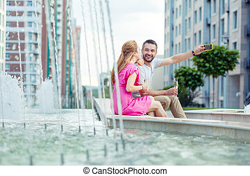 Nice positive man sitting together with his girlfriend