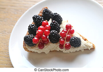 Beautiful photo of delicious cheese cheesecake with blackberries and red currants close up