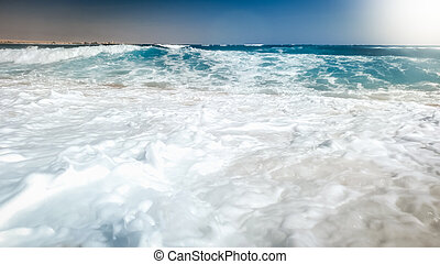 Beautiful photo of sea waves rolling on the sea beach. Perfect background for your summer holiday vacation