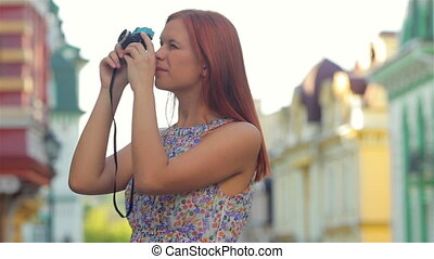 Beautiful photographer girl with an vintage retro camera.