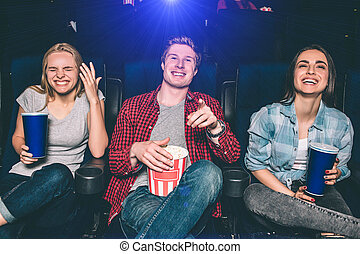 Beautiful picture of happy people laughing in ciname hall. They are looking on screen and smiling. Girls and guy look absolutely stunning and happy.