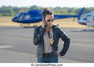 beautiful pilot using a phone in the background an helicopter