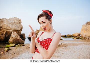 Beautiful pin up girl in red swimsuit pointing finger away -...