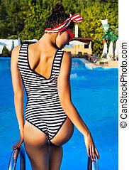 Beautiful pin up girl near the swimming pool