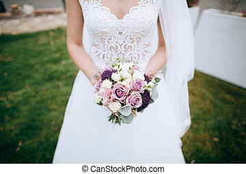 Beautiful pink and white wedding bouquet in hands of the bride