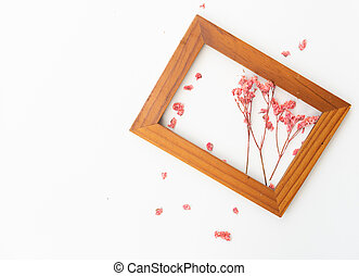 Beautiful pink dried flowers decorated with brown wooden frame isolated on white background, top view