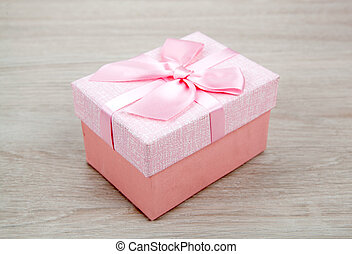 beautiful pink gift box on wooden background