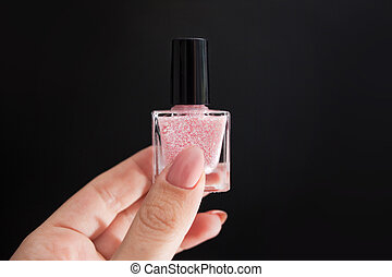 Beautiful pink manicure with gold decor. Womens hand holding...