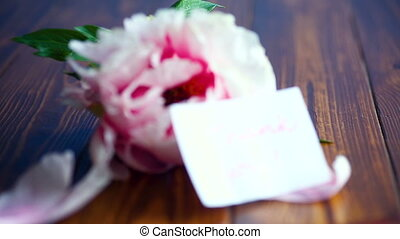 beautiful pink peony on a wooden table