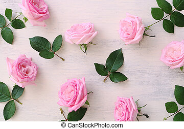 Beautiful pink roses on white wooden background