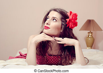 beautiful pinup girl with red lipstick having fun relaxing in bed looking up, portrait on light copy space background