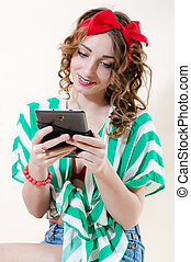Beautiful pinup woman holding tablet pc computer & happy smiling over white background