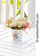 Beautiful plastic flowers in metal vase.
