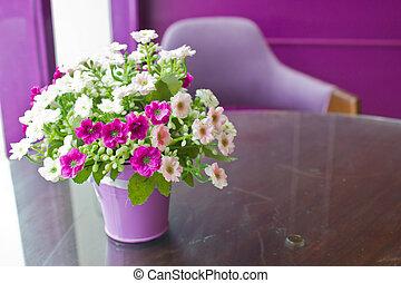 Beautiful plastic flowers in metal vase with copy space.