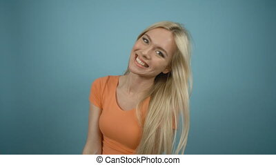 Beautiful playful laughing woman with long blonde hair posing in orange T-shirt against a blue background