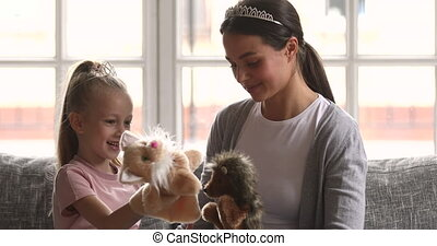 Beautiful playful mum and kid daughter playing puppet toys