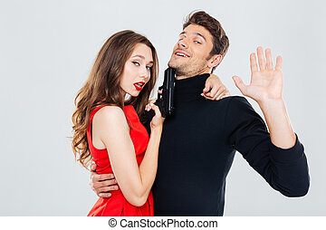 Beautiful playful young couple standing and posing with gun