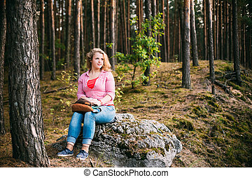Beautiful Plus Size Young Smiling Woman Sitting on Stone inSumme