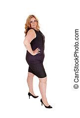 Beautiful plus sized woman standing in a black dress