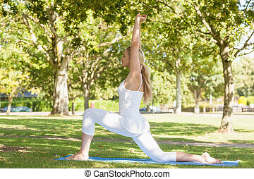 Beautiful ponytailed woman stretching in a yoga pose