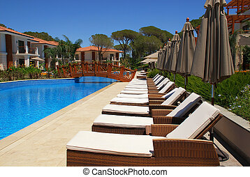Beautiful poolside with line of chaise lounges