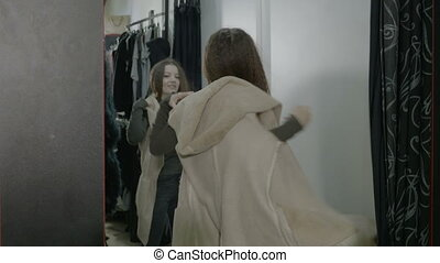 Beautiful popular woman shopping trying clothes in the fitting room and looking in the mirror