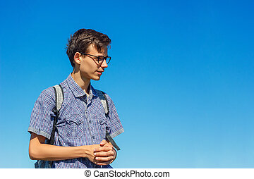 beautiful portrait of a young man with glasses on a blue sky background