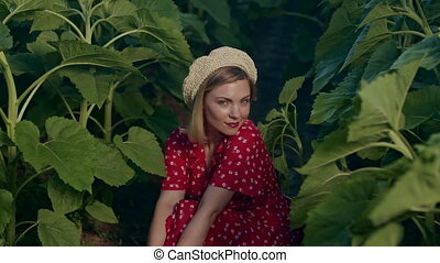 Beautiful portrait of attractive blonde woman in straw beret hat . Girl sitting between plants.nature background. Retro floral dress, red lips. Pleasant feminine appearance, kind smile